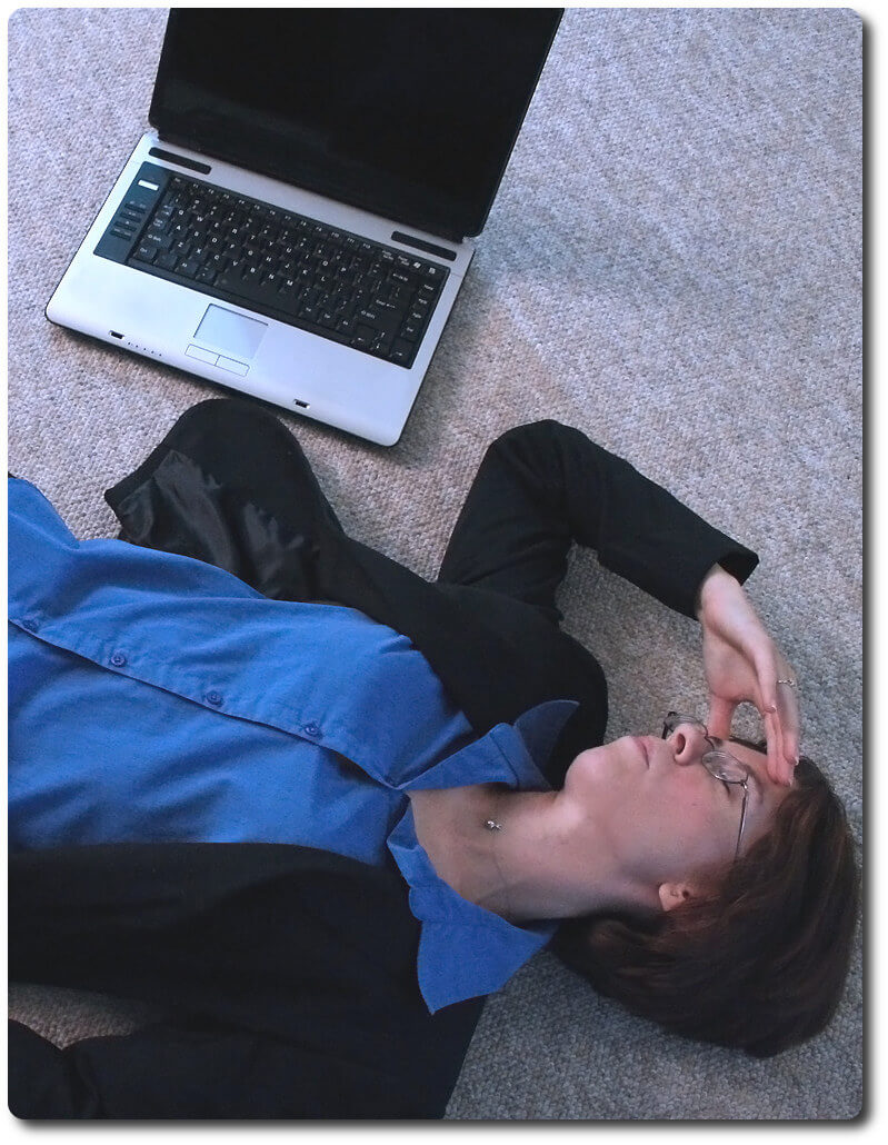 Frustrated woman holding head and laying on floor next to laptop