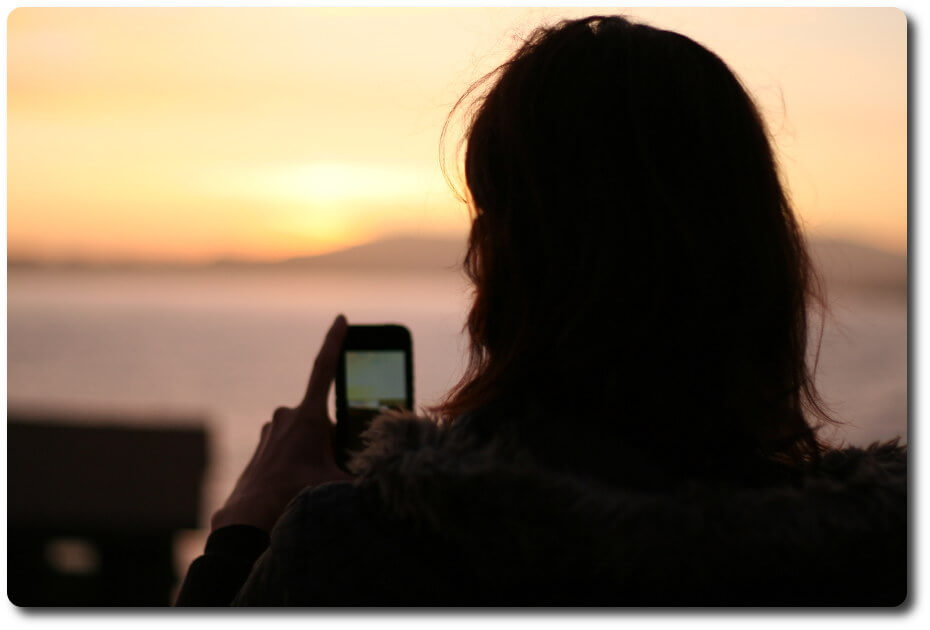 Woman using a cellphone during a sunset